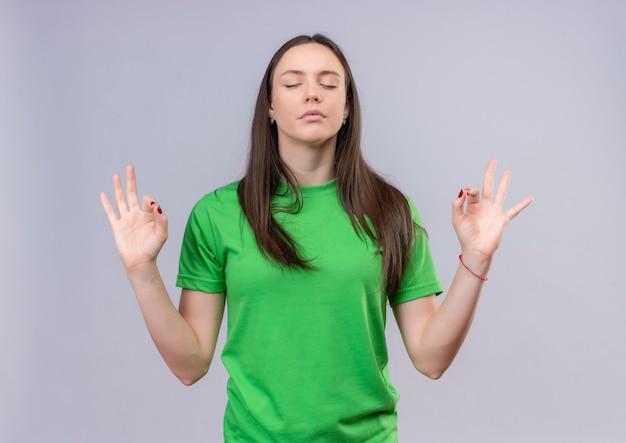 Belle jeune fille portant un t-shirt vert se détendre avec les yeux fermant faisant le geste de méditation avec les doigts debout sur fond blanc isolé