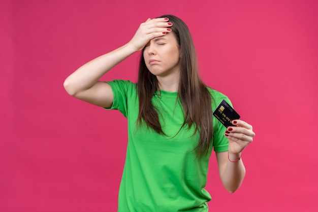Belle jeune fille portant un t-shirt vert tenant une carte de crédit tenant sa tête avec la main pour erreur bouleversée avec les yeux fermés debout sur fond rose isolé