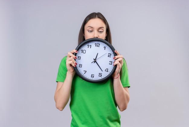 Belle jeune fille portant un t-shirt vert tenant une horloge avec un regard perplexe debout sur fond blanc isolé