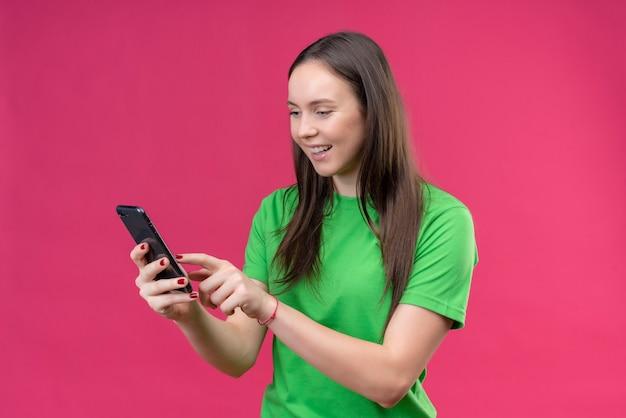 Belle jeune fille portant un t-shirt vert tenant un smartphone bavardant avec quelqu'un heureux et positif souriant debout sur fond rose isolé
