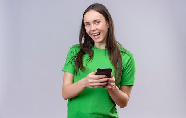 Belle jeune fille portant un t-shirt vert tenant un smartphone regardant la caméra en souriant joyeusement debout sur fond blanc isolé