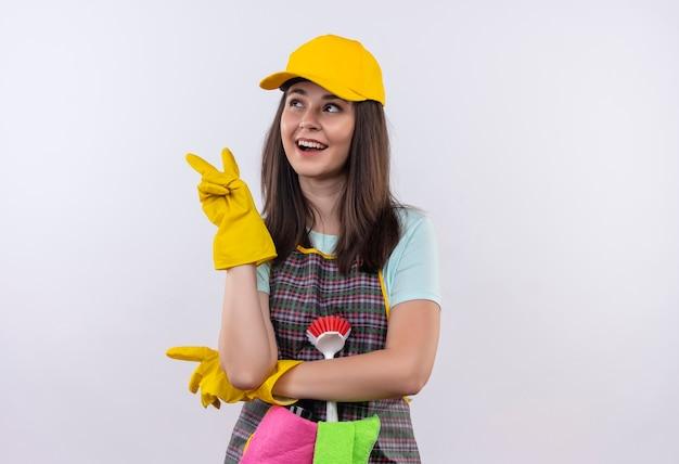 Belle jeune fille portant un tablier, une casquette et des gants en caoutchouc souriant joyeusement à côté montrant le signe de la victoire