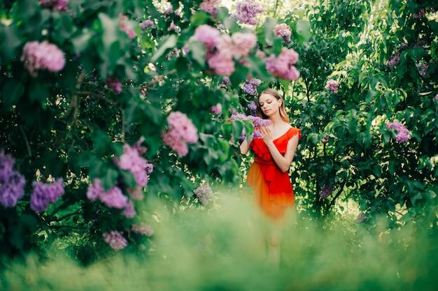 Belle jeune fille posant parmi l'arbre en fleurs