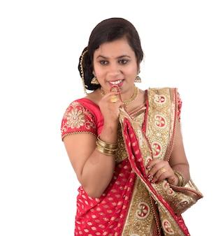 Belle jeune fille posant en sari traditionnel indien sur blanc.