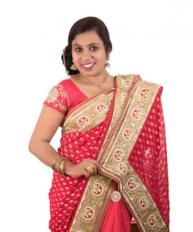 Belle jeune fille posant en sari traditionnel indien sur fond blanc.