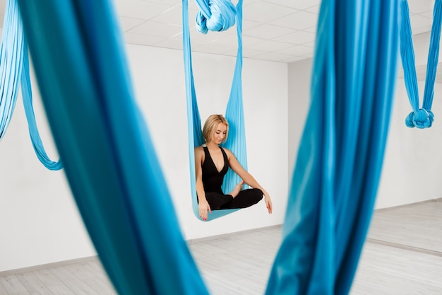 Belle jeune fille pratiquant le yoga aérien dans la salle de gym.
