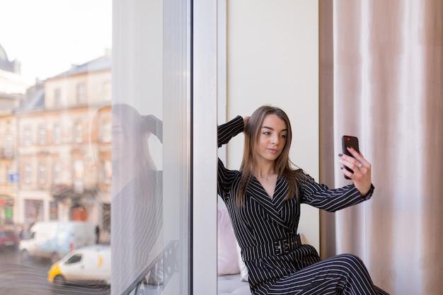 Belle jeune fille prenant un selfie avec téléphone sur le rebord de la fenêtre de l'hôtel contre la ville