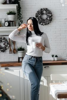 Belle jeune fille prend le petit déjeuner et boit du café dans la cuisine. mode de vie.