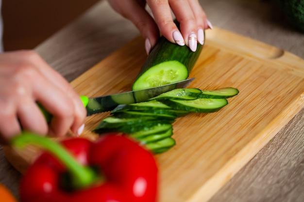 Belle jeune fille prépare une salade diététique saine