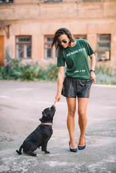 Belle jeune fille promener son chien de compagnie staffordshire bull terrier à l'extérieur par une journée ensoleillée en été. entraînement des animaux.