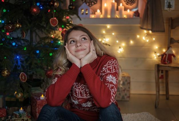 Belle jeune fille en pull rouge sur l'arbre de noël. intérieur festif, bougies, lumières, guirlandes. portrait d'une jeune fille la nuit de noël