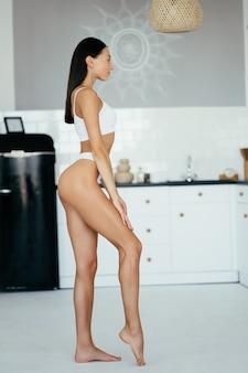 Belle jeune fille qui pose en lingerie dans la cuisine