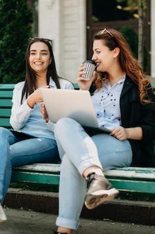 Belle jeune fille racontant des histoires à sa petite amie de taille plus alors qu'elle était assise sur un banc à l'extérieur de la ville.