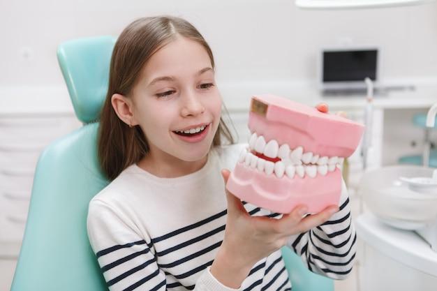 Belle jeune fille regardant grand modèle de mâchoire, assis dans un fauteuil dentaire