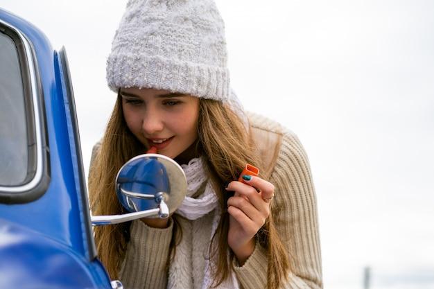 Belle jeune fille regarde dans le rétroviseur de voiture et maquille ses lèvres