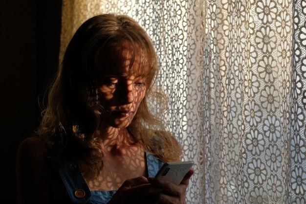 Belle jeune fille regarde le téléphone le jeu de lumière et d'ombre sur le corps. image d'ombre légère.