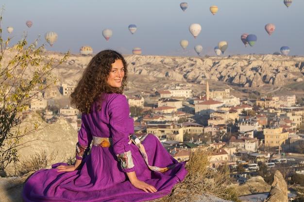 Belle jeune fille regarde le vol de ballons en cappadoce sur le point de vue