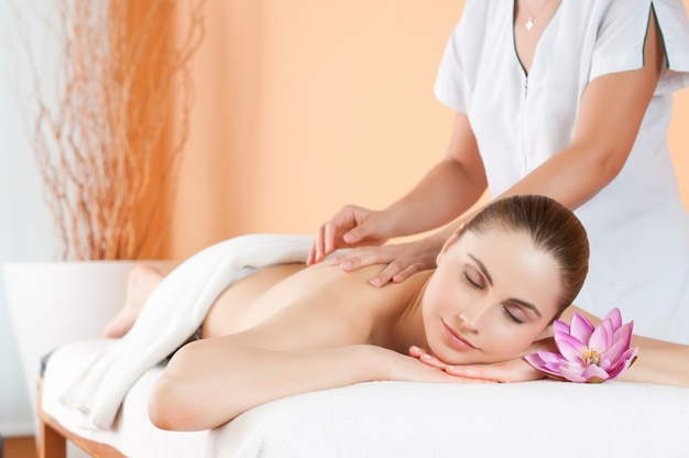 Belle jeune fille relaxante avec massage des mains au spa pendant un soin de beauté