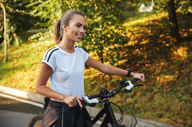 Belle Jeune Fille De Remise En Forme Marchant à Vélo Sur La Route Du Parc Photo Premium