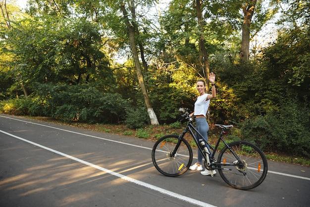 Belle jeune fille de remise en forme marchant à vélo sur la route du parc