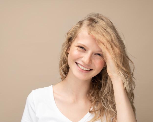 Belle jeune fille en riant. jolie blonde aux cheveux bouclés en t-shirt blanc contre un mur beige