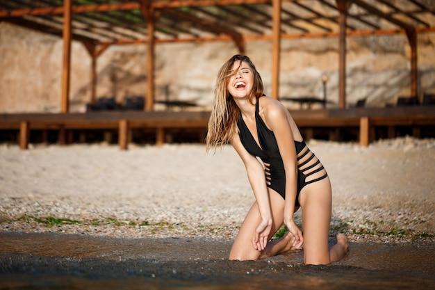 Belle jeune fille riante reste sur la plage du matin
