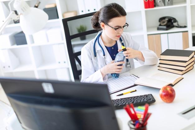 Une belle jeune fille en robe blanche est assise à un bureau d'ordinateur, tient un marqueur dans sa main et ouvre une bouteille d'eau.