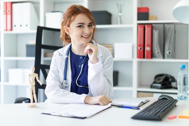 Une belle jeune fille en robe blanche est assise à une table dans le bureau.