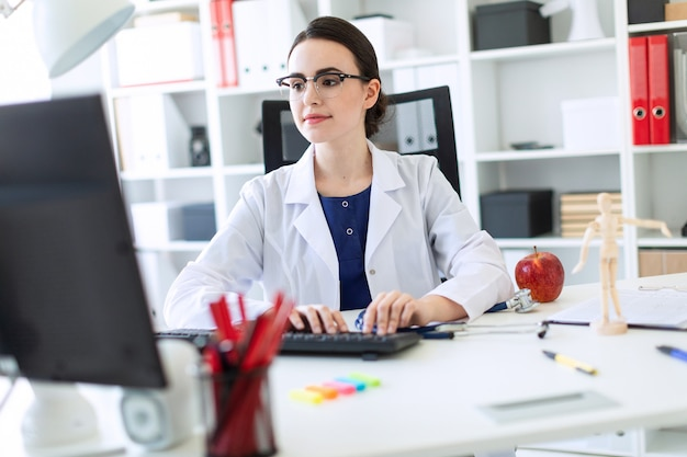 Une belle jeune fille en robe blanche est assise à la table et tape sur le clavier.