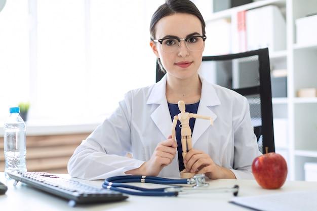 Une belle jeune fille en robe blanche est assise à une table et tient une figure en bois d'un homme dans ses mains