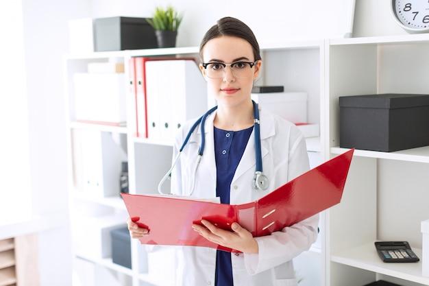 Une belle jeune fille en robe blanche se tient près de l'abri et feuillette un dossier rouge avec des documents.