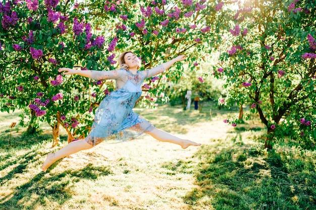 Belle jeune fille en robe bleue sautant dans le parc ensoleillé
