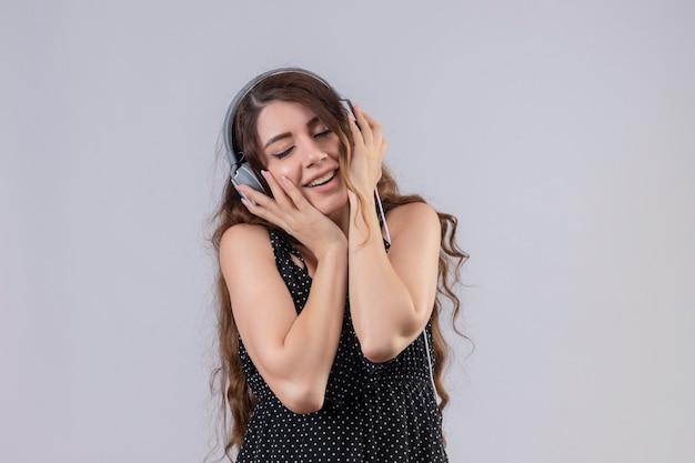 Belle jeune fille en robe à pois appréciant la musique préférée grâce à des écouteurs sans fil debout avec les yeux fermés sur fond blanc
