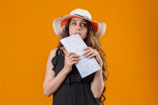 Belle jeune fille en robe à pois en chapeau d'été tenant la carte à côté avec une expression pensive debout sur fond jaune