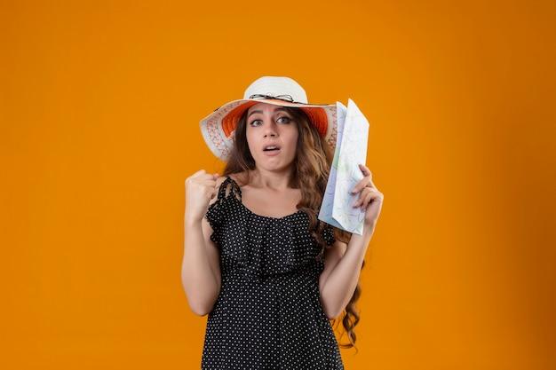 Belle jeune fille en robe à pois en chapeau d'été tenant la carte levant le poing confus avec une expression sceptique sur le visage debout sur fond jaune