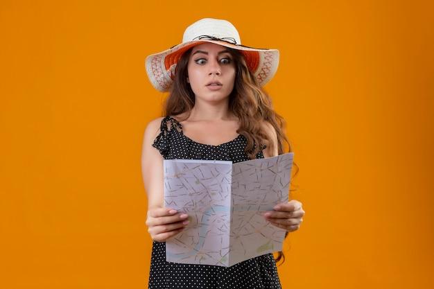 Belle jeune fille en robe à pois en chapeau d'été tenant la carte regardant étonné et choqué debout sur fond jaune