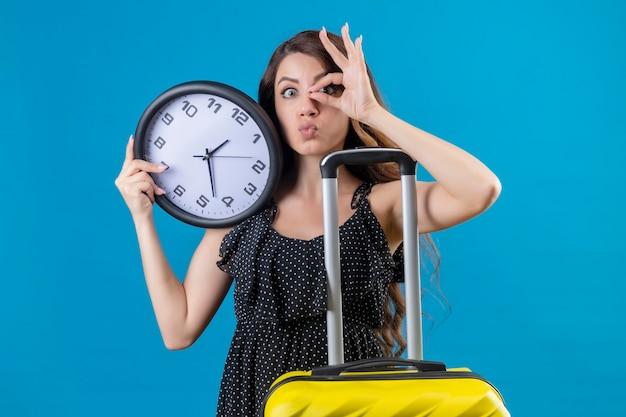 Belle jeune fille en robe à pois debout avec valise tenant horloge faisant signe ok regardant la caméra à travers ce signe positif et heureux sur fond bleu