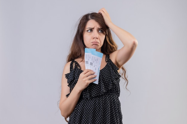 Belle jeune fille en robe à pois tenant un billet d'avion à la mécontentement avec une expression triste sur le visage debout sur fond blanc