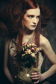 Belle jeune fille avec des roses sèches en décoration, maquillage créatif, concept artistique