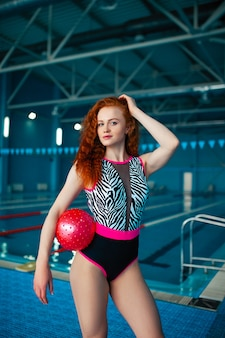 Belle jeune fille rousse dans la piscine couverte