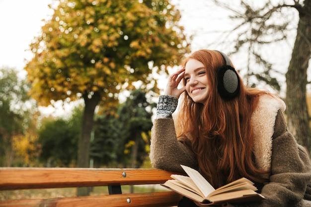 Belle jeune fille rousse écoutant de la musique avec des couvre-chefs assis sur un banc, lisant un livre