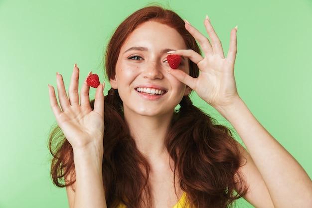 Belle jeune fille rousse émotionnelle posant isolée sur fond de mur vert avec framboise.