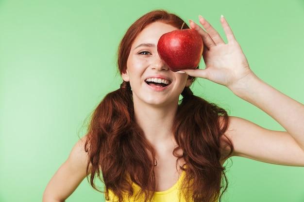 Belle jeune fille rousse émotionnelle posant isolée sur fond de mur vert avec pomme.
