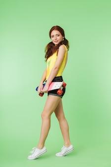 Belle jeune fille rousse heureuse posant isolée sur fond de mur vert avec planche à roulettes.