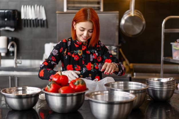 Belle jeune fille rousse en robe de soirée prépare des plats dans une cuisine professionnelle