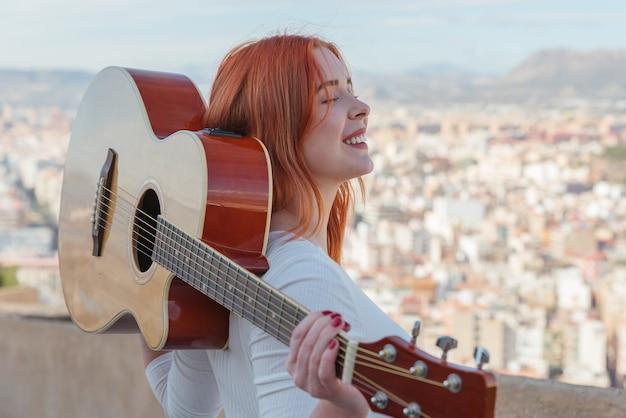 Belle jeune fille rousse se promène avec sa guitare à l'extérieur qui offre une vue panoramique sur la ville.