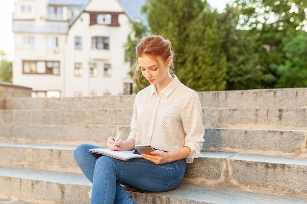 Belle jeune fille rousse avec des taches de rousseur assis sur un escalier