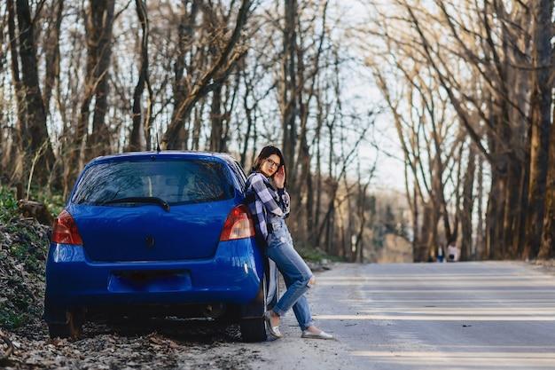 Belle jeune fille sur la route près de la voiture