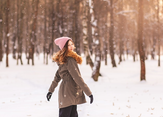 Belle jeune fille s'amusant en hiver dans le parc par une journée ensoleillée