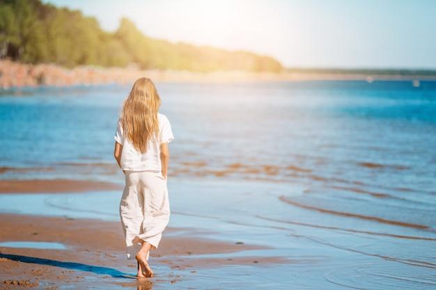 Belle jeune fille s'amuser au bord de mer tropical.